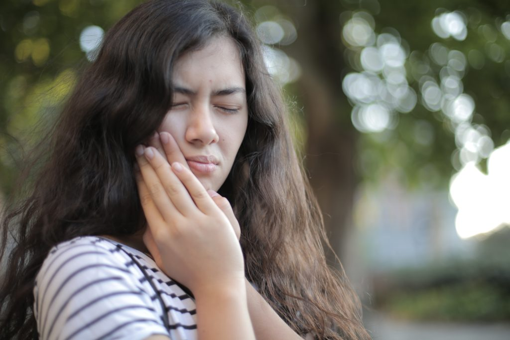 woman with tmj pain holding jaw in pain